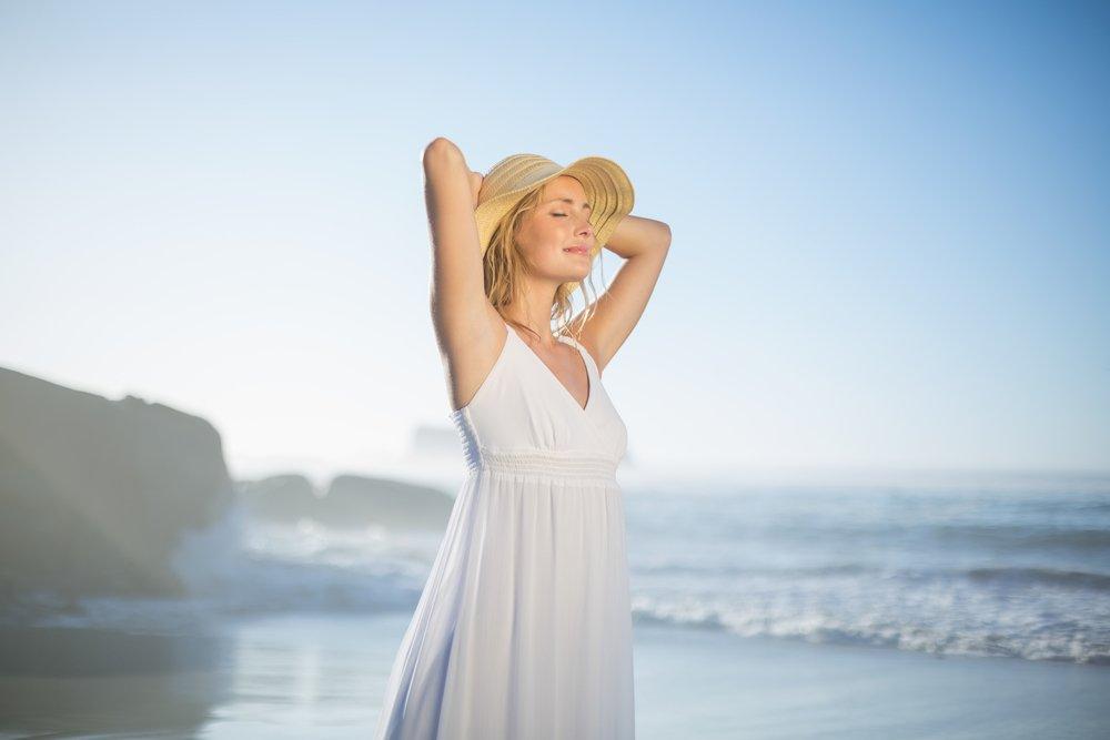 frau steht in weißem sommerkleid am strand