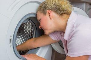 frau putzt trommel der waschmaschine