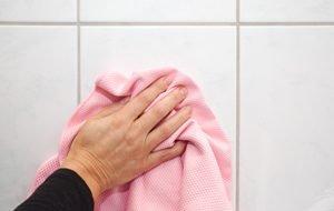 hand wischt fliesen mit rosa tuch