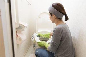 frau mit handschuhen putzt toilette