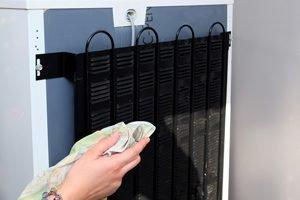 hand mit tuch putzt kühlschrank rückseite