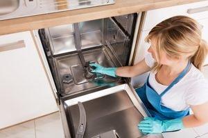 frau nimmt filter aus spülmaschine