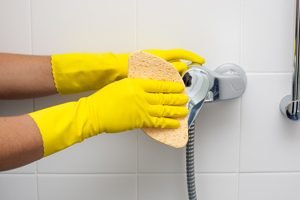 Hände in Putzhandschuhen reinigen Duscharmatur mit Schwamm