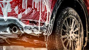 rotes Auto ist mit Autoshampoo eingeschäumt