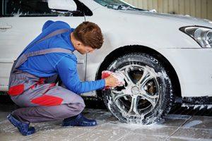 Mann reinigt Felge eines Autos