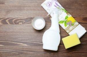 Backpulver, eine Sprühflasche, ein Schwamm und eine Serviette mit Zitronen darauf