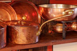 mehrere Kupfertöpfe in einer Küche
