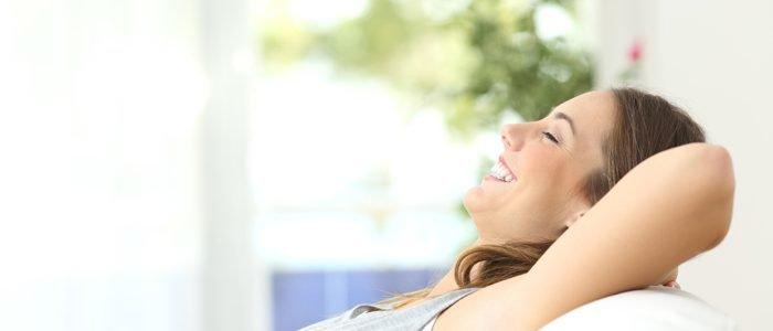 lachende Frau sitzt auf Sofa