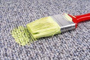 ein Pinsel mit gelber Farbe liegt auf einem Teppich