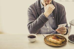 Mann sitzt mit Smartphone beim Essen