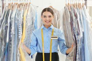 Angestellte in reinigung lächelt zwischen Hemden