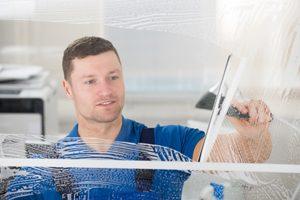 Mann benutzt Abzieher an gereinigtem Fenster