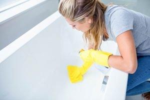 Frau mit gelben Handschuhen putzt Badewanne