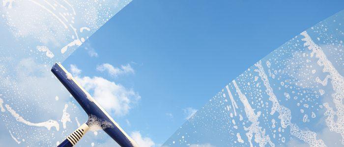 Abzieher zieht über eingeseiftes Fenster, dahinter blauer Himmel