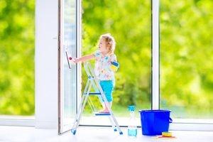 Mädchen steht auf Leiter und putzt Fenster