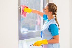 Frau putzt Fenster mit rosa Lappen