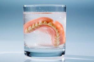 Ein Gebiss schwimmt mit einer Tablette in einem Glas
