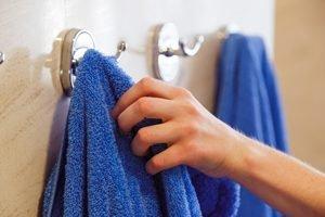 eine Hand greift nach einem von zwei blauen Handtüchern