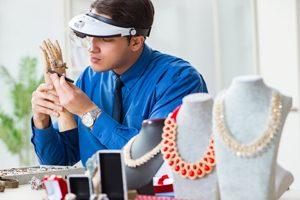Juwelier mit Arbeitsgerät und Schmuck