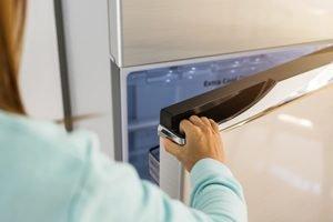 Hand öffnet Kühlschranktür