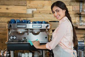 Frau wischt lächelnd über Kaffeemaschine