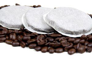 Kaffeepads liegen auf Kaffeebohnen auf weißem Grund