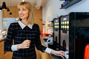 Frau stellt Tasse in Kaffeevollautomat