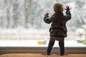 Kleinkind steht an Fenster und fasst gegen die Scheibe