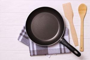 Teflonpfanne auf Küchentuch mit Holzlöffel