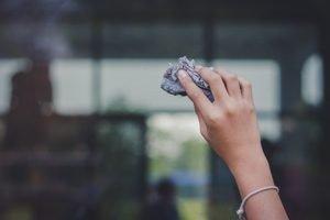 Hand putzt Fenster mit Zeitungspapier