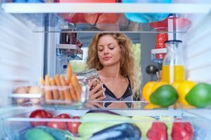 lächelnde Frau nimmt Essen aus sauberem Kühlschrank.