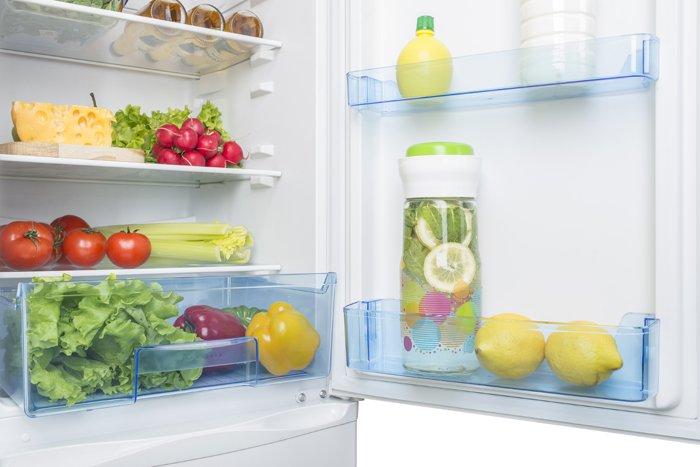 offener, sauberer Kühlschrank mit Gemüse und Zitronenwasser