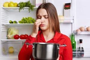 junge Frau blick vor offenen Kühlschrank angewidert in einen Topf und hält sich die Nase zu