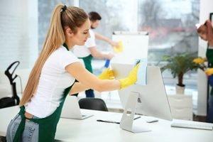 junge Frau reinigt Computer mit Tuch