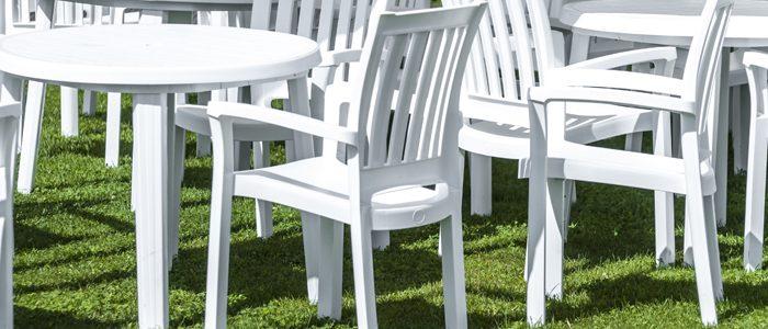 weiße Gartentische und -stühle auf einer Wiese