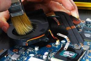 weicher Pinsel streicht über Kühlsystem des Laptops