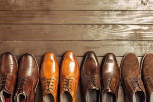 vier paar Lederschuhe stehen auf einem Holzfußboden