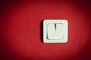 weißer Lichtschalter an roter Wand