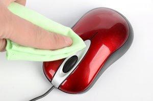 Finger mit Tuch putzt rote Maus