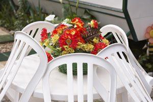 weiße Stühle lehnen an weißem Tisch mit Blumen in der Mitte