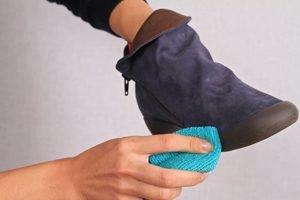 zwei Hände reinigen einen Wildlederschuh mit einem Tuch