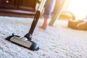 barfüßige Frau saugt Staub auf einem hellen Teppich