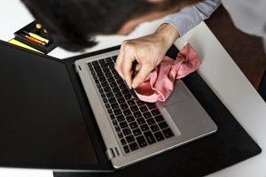 Mann putzt mit weichem Tuch Tastatur am Laptop