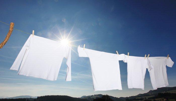 weiße Wäsche auf einer Leine vor blauem Himmel
