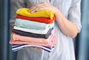 Frau hält einen Stapel gefalteter Wäsche