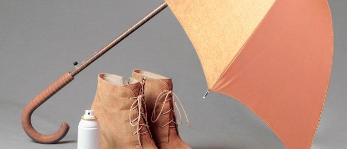 braune Wildlederstiefeletten und Spraydose unter Schirm auf grauem Grund