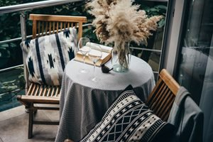 kleiner Tisch mit zwei Stühlen auf einem Balkon