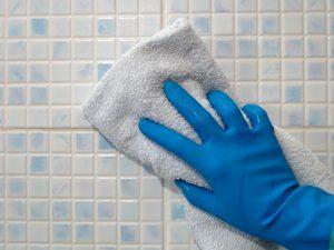 Hand in blauem Putzhandschuh trocknet Fliesen mit Handtuch