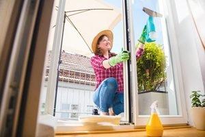 Frau mit Strohhut putzt Glastür auf dem Balkon