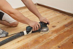 Mann schleift einen Holzboden ab